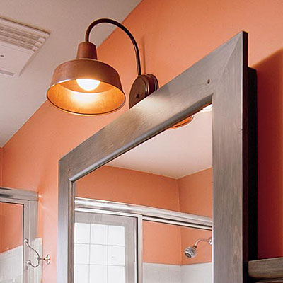 bold bronze lighting and mirror in small bathroom